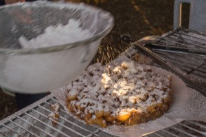 dusting funnel cake with icing
