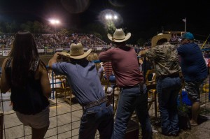 men watching rodeo competitions